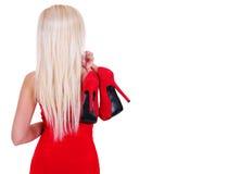 Giovane donna bionda che giudica le scarpe rosse sexy del tacco alto isolate Fotografia Stock Libera da Diritti