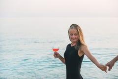 Giovane donna bionda che gode del vetro di vino rosato e che tiene la mano dell'uomo sulla spiaggia dal mare al tramonto Fotografia Stock