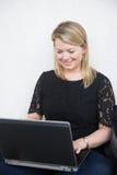 Giovane donna bionda che lavora ad un computer portatile Immagini Stock
