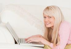 Giovane donna bionda che si distende con un computer portatile Fotografia Stock Libera da Diritti