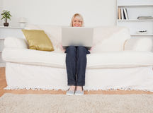 Giovane donna bionda che si distende con un computer portatile su un SOF Immagine Stock Libera da Diritti