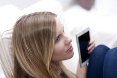 Giovane donna bionda che si rilassa con la compressa in sua mano fotografia stock libera da diritti