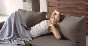 Giovane donna bionda che si rilassa sullo strato Immagini Stock