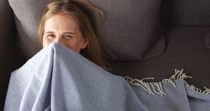 Giovane donna bionda che si rilassa sullo strato Immagini Stock Libere da Diritti