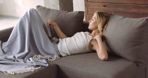 Giovane donna bionda che si rilassa sullo strato Fotografie Stock