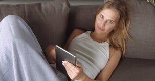 Giovane donna bionda che si rilassa sullo strato Fotografia Stock