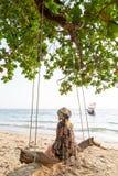 Giovane donna bionda che si siede su un'oscillazione di legno alla spiaggia di Krabi Railey che trascura la barca della coda lung immagini stock