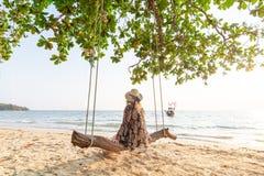 Giovane donna bionda che si siede su un'oscillazione di legno alla spiaggia di Krabi Railey che trascura la barca della coda lung fotografia stock libera da diritti