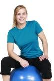 Giovane donna bionda che si siede sulla palla di esercizio isolata su bianco Fotografia Stock
