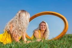 Giovane donna bionda che si trova nell'erba con lo specchio fotografie stock libere da diritti