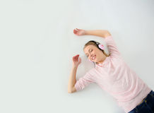 Giovane donna bionda che si trova sulla musica d'ascolto del pavimento Immagine Stock Libera da Diritti
