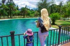 Giovane donna bionda che sta con un bambino su un ponte e che esamina uno stagno fotografia stock libera da diritti