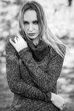 Giovane donna bionda che sta in un parco con i colori di autunno Fotografia Stock