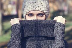 Giovane donna bionda che sta in un parco con i colori di autunno Immagine Stock