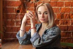 Giovane donna bionda che tiene tazza di carta arancio con la paglia del cocktail che si siede vicino alla finestra contro il muro Immagini Stock Libere da Diritti