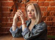 Giovane donna bionda che tiene tazza di carta arancio con la paglia del cocktail che si siede vicino alla finestra contro il muro Fotografia Stock Libera da Diritti