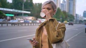 Giovane donna bionda con il caffè di breve taglio di capelli ed il bus il telefono bevente di tenuta, il taxi aspettante o stock footage