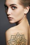 Giovane donna bionda con il tatuaggio fotografia stock libera da diritti