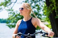 Giovane donna bionda con la bicicletta fotografie stock