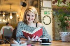 Giovane donna bionda con un libro immagini stock