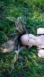 Giovane donna bionda del ritratto che risiede nell'erba con capelli e gli occhi azzurri lunghi che cerca felice fotografie stock