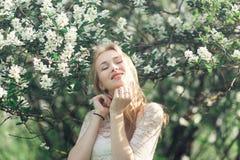 Giovane donna bionda delicata in giardino di fioritura Ragazza che gode della fragranza della molla Ha coperto il vestito di pizz Fotografia Stock