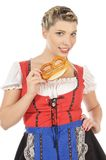 Giovane donna bionda in dirndl che mangia ciambellina salata Immagine Stock