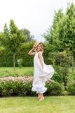 Giovane donna bionda felice che cammina a piedi nudi sull'erba verde Immagine Stock