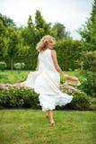 Giovane donna bionda felice che cammina a piedi nudi sull'erba verde Fotografie Stock