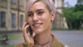 Giovane donna bionda felice con il piercing e capelli di scarsità che parlano sul telefono e che sorridono, università vicina sta video d archivio
