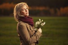 Giovane donna bionda felice di modo che indossa camminata beige classica del cappotto all'aperto fotografie stock