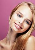 Giovane donna bionda graziosa con la fine dell'acconciatura alta ed il trucco su fondo rosa Immagine Stock