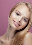 Giovane donna bionda graziosa con la fine dell'acconciatura su Immagini Stock
