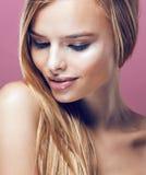 Giovane donna bionda graziosa con la fine dell'acconciatura su Fotografia Stock