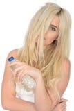 Giovane donna bionda naturale in buona salute adatta che tiene una bottiglia di acqua minerale Fotografia Stock Libera da Diritti