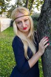 Giovane donna bionda nel parco vicino all'albero Immagini Stock