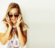 Giovane donna bionda in occhiali da sole che sorride vicino sull'isolato su su bianco Immagini Stock