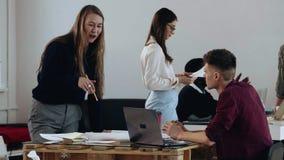Giovane donna bionda professionale felice di affari che parla con responsabile maschio al computer portatile Posto di lavoro legg stock footage