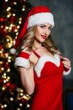 Giovane donna bionda sexy in costume rosso di Santa Claus con le scarpe rosse e la tazza bianca di sorridere del caffè del tè immagini stock