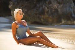 Giovane donna bionda sexy e rilassata in costume da bagno di un pezzo che si siede sulla sabbia che esamina mare che gode delle v immagini stock