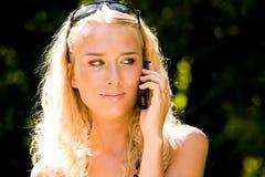 Giovane donna bionda sorridente che comunica sul telefono mobile Fotografia Stock