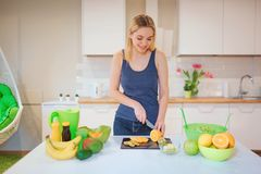 Giovane donna bionda sorridente che cucina frutta fresca nella cucina Alimento sano Pasto vegetariano Disintossicazione di dieta fotografie stock libere da diritti