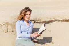 Giovane donna bionda sorridente che legge un libro Immagini Stock Libere da Diritti