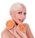 Giovane donna bionda sorridente con la frutta arancio isolata immagine stock libera da diritti