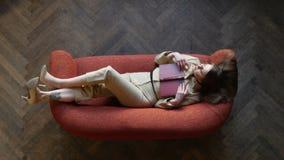 Giovane donna bionda splendida in vetri e vestito beige sui libri e vago sull'esaminare di lettura rossi del sofà video d archivio