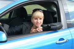 Giovane donna bionda in un'automobile. Immagine Stock