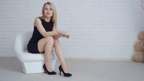 Giovane donna bionda in vestito nero che si siede nella sedia stock footage