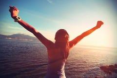 Giovane donna a braccia aperte alla spiaggia di alba Immagini Stock