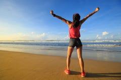 Giovane donna a braccia aperte sulla spiaggia della spiaggia di alba Fotografia Stock