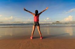 Giovane donna a braccia aperte sulla spiaggia della spiaggia di alba Fotografia Stock Libera da Diritti
